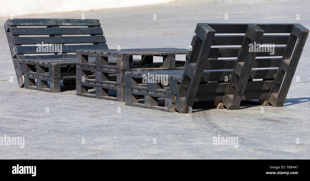 Table and chairs of pallets on the sidewalk, painted in black, the concept of street furniture - Stock Image