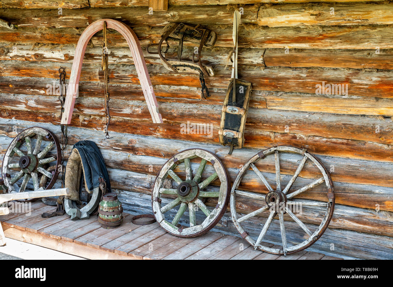 Vintage horse harnesses and wagon wheels next the barn wall in russian village - Stock Image