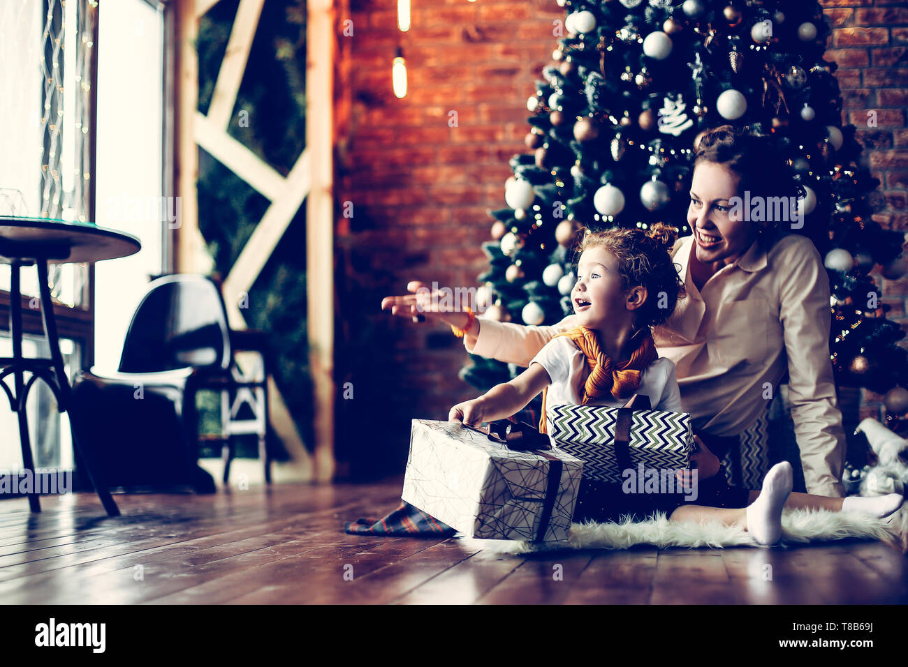 little girl kisses her mother near the Christmas tree . the concept of Christmas - Stock Image