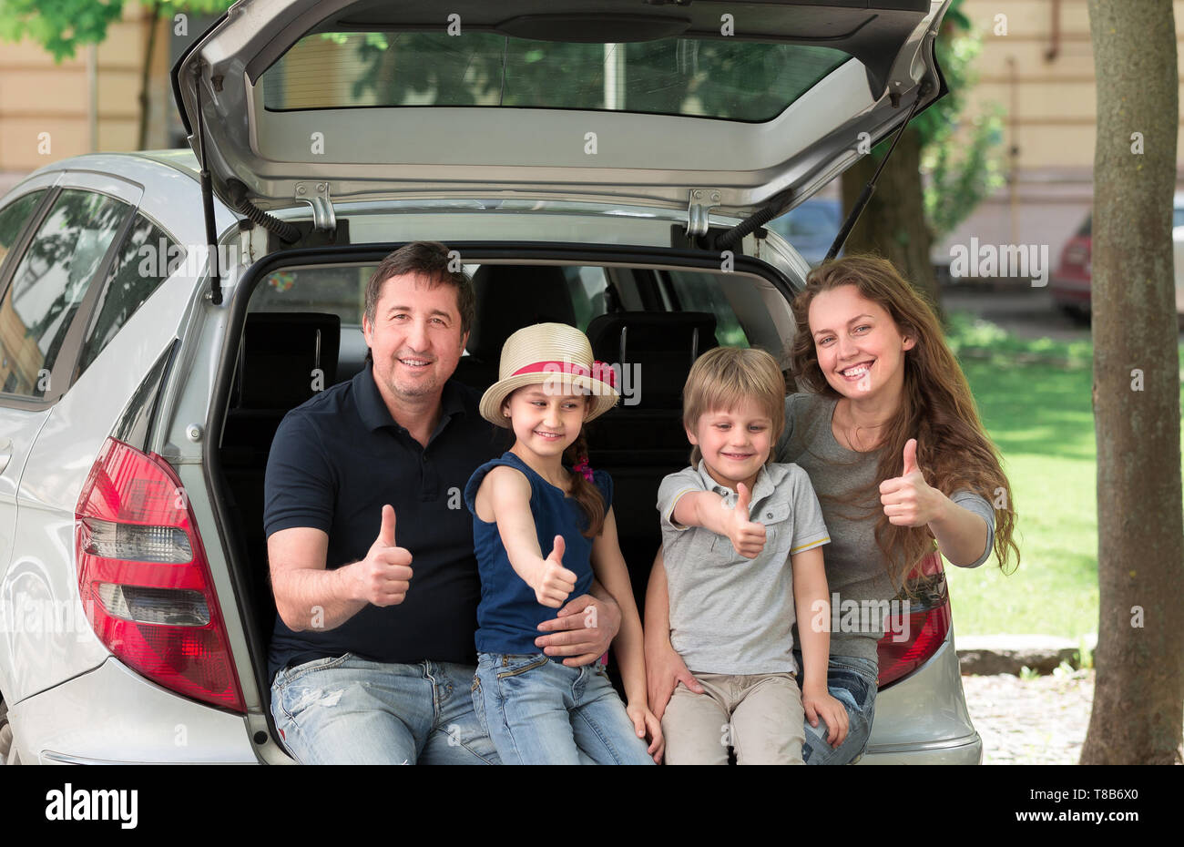 happy family sitting in the trunk of a car and showing thumbs up . the concept of family travel - Stock Image
