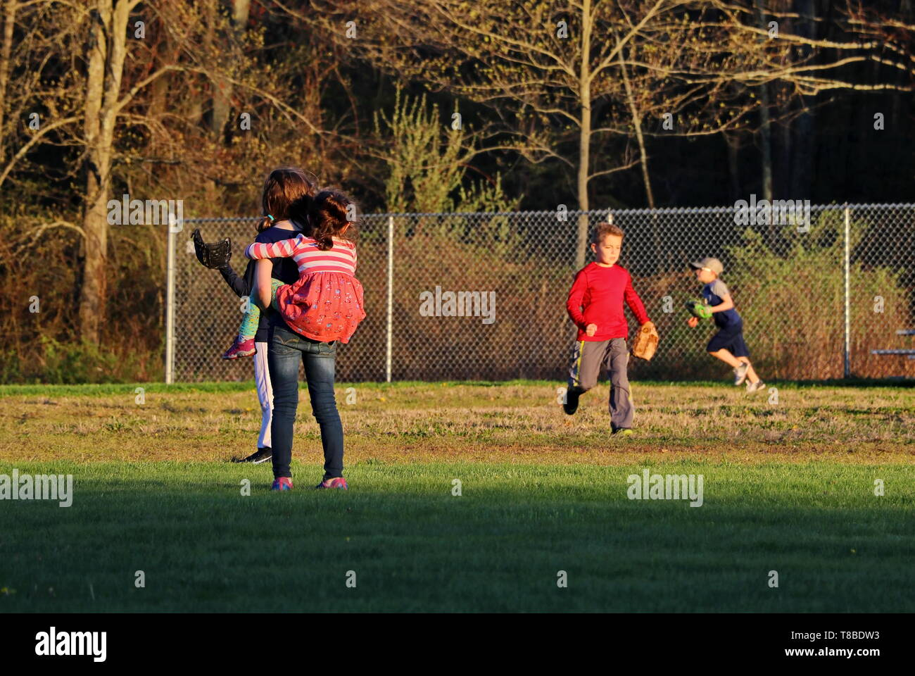older sister gives youngest a piggy-back while they both look at boys playing baseball - Stock Image