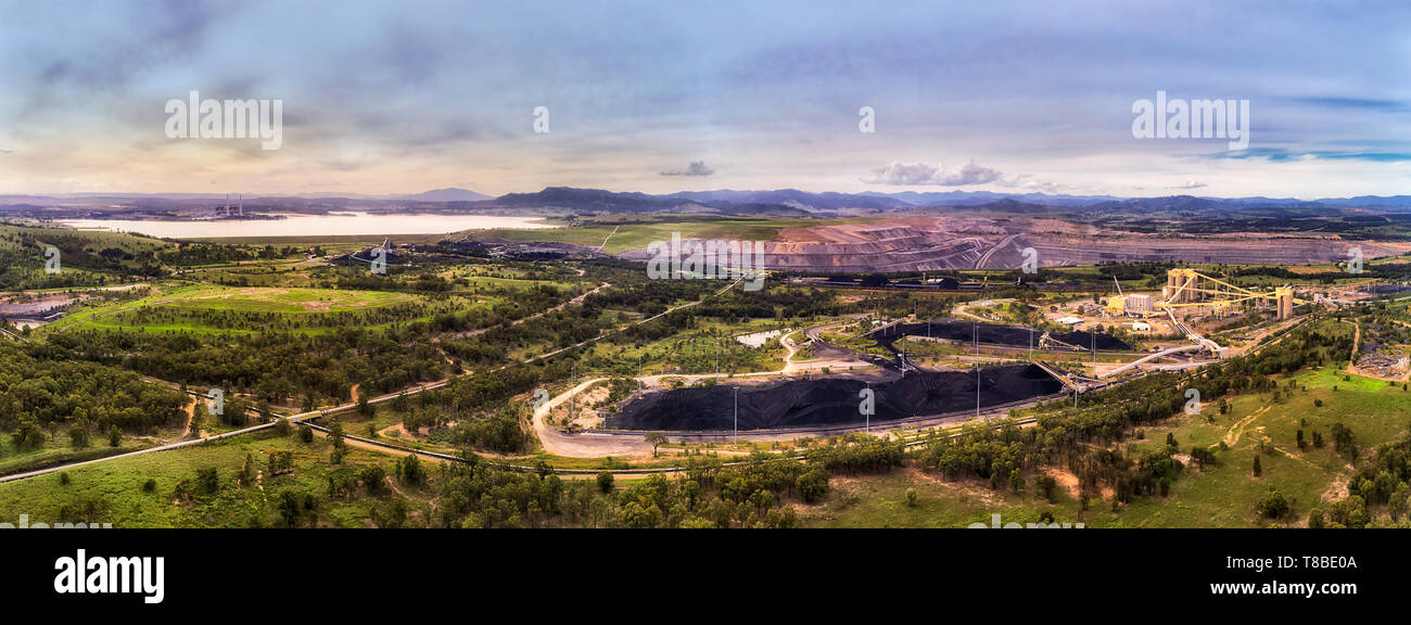 Bulk storage of black coal extracted from open cut mine near Liddell Power station and Liddell lake in Hunter valley coal basin of NSW, Australia. - Stock Image
