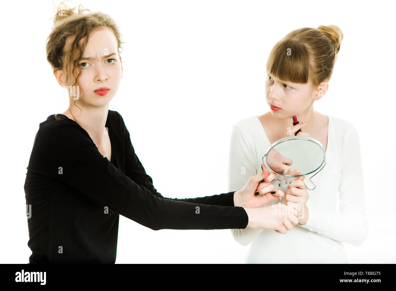 Two puberty girls in black and white dresses haggle to get a mirror to make a make up - sister rivalry - white background - Stock Image