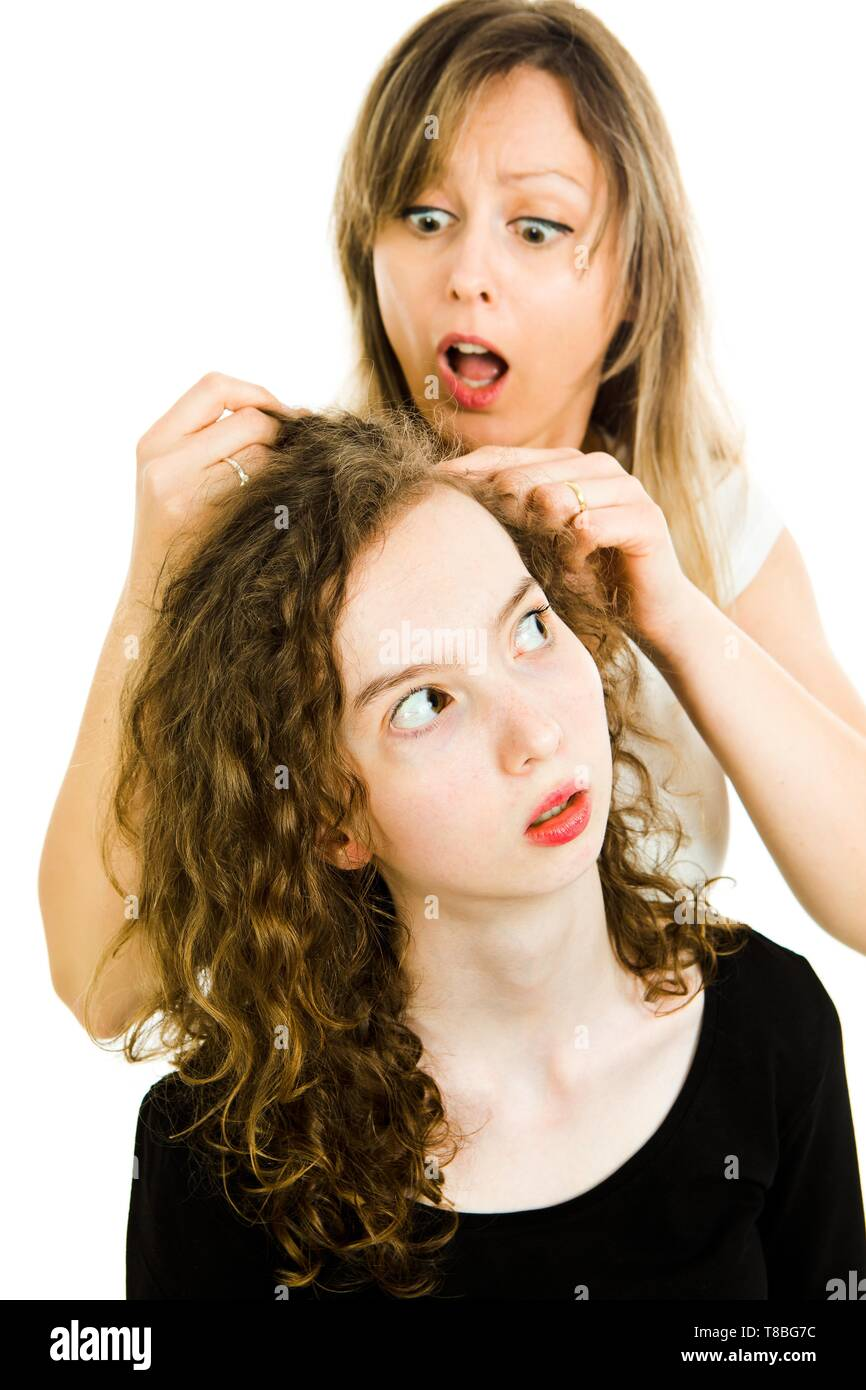 Mother checking child's head for lice showing emotion of surprise, consternation and dismay - louse on head, curly hairs - white background Stock Photo