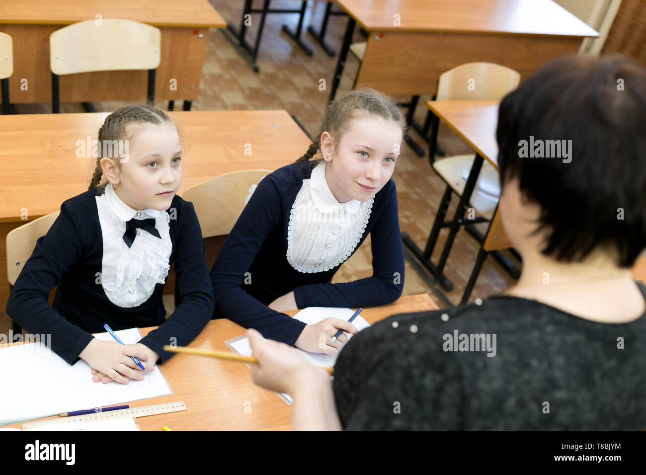 Teenage girls classmates sit at table and with fear look at the school teacher. - Stock Image