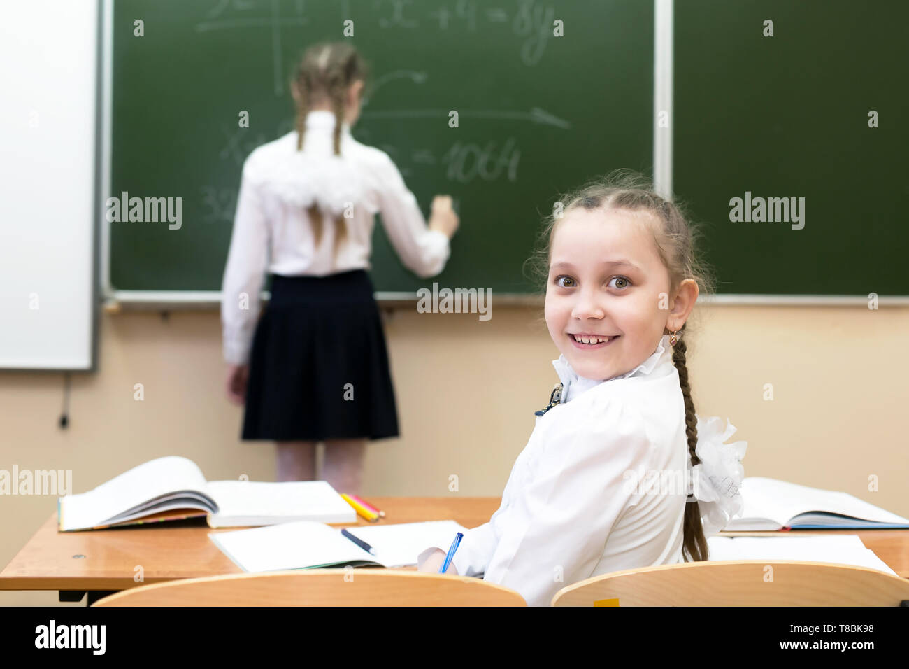 A schoolgirl girl looks into the camera while her friend, a classmate, answers the teacher at the blackboard - Stock Image