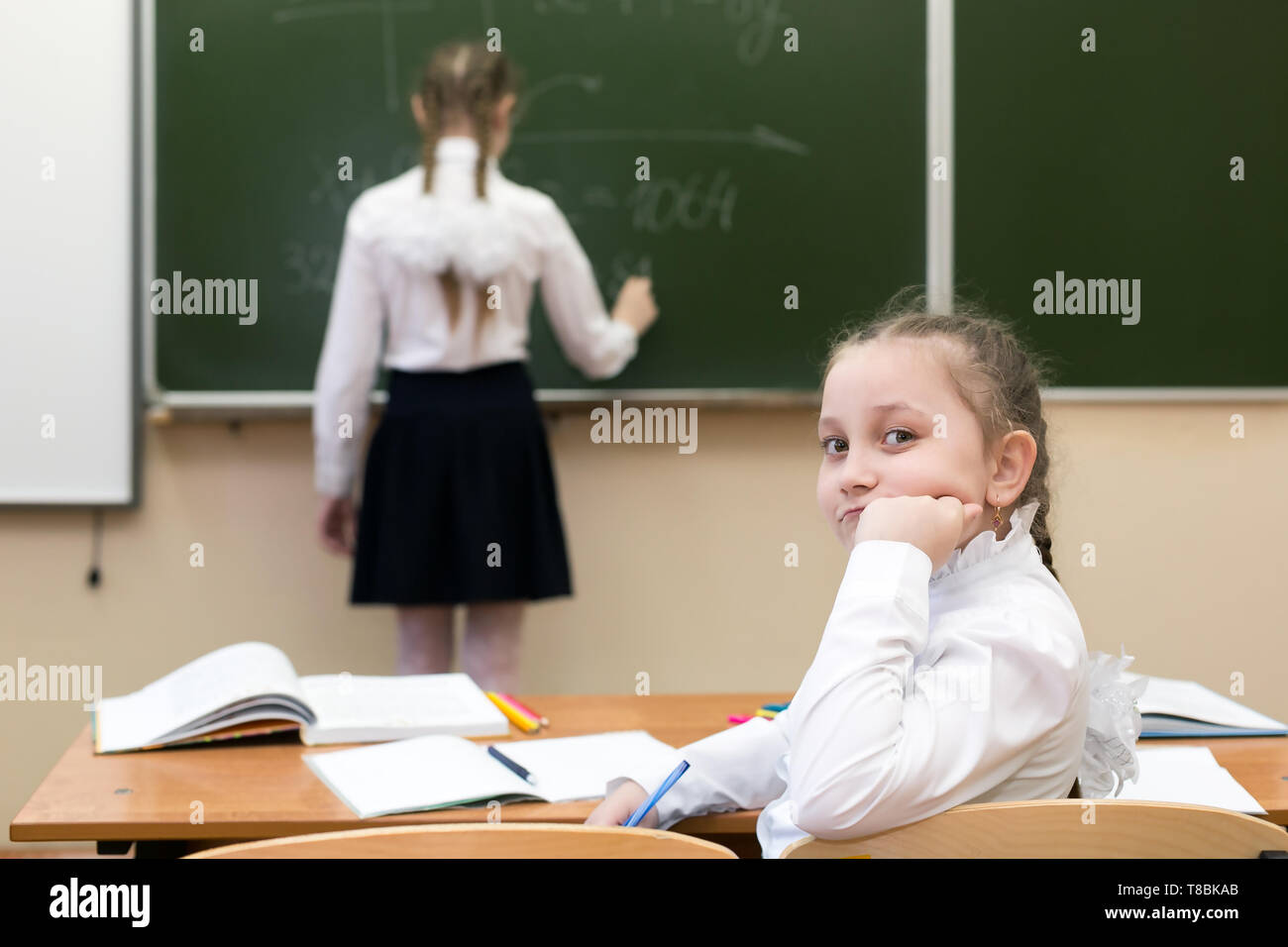 schoolgirl girl looks into the camera while her friend, a classmate, answers the teacher at the blackboard. - Stock Image