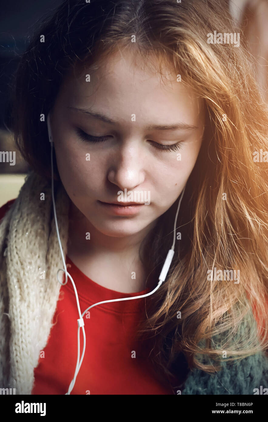 A long-haired beautiful girl in a red t-shirt rides in public transport near the window, from which the sunlight shines, and listens to music in headp - Stock Image