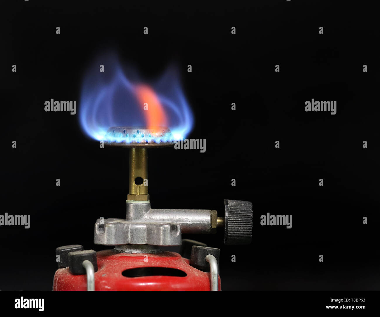 Flame of a gas burner, cartridge burner on black background with copy space - Stock Image