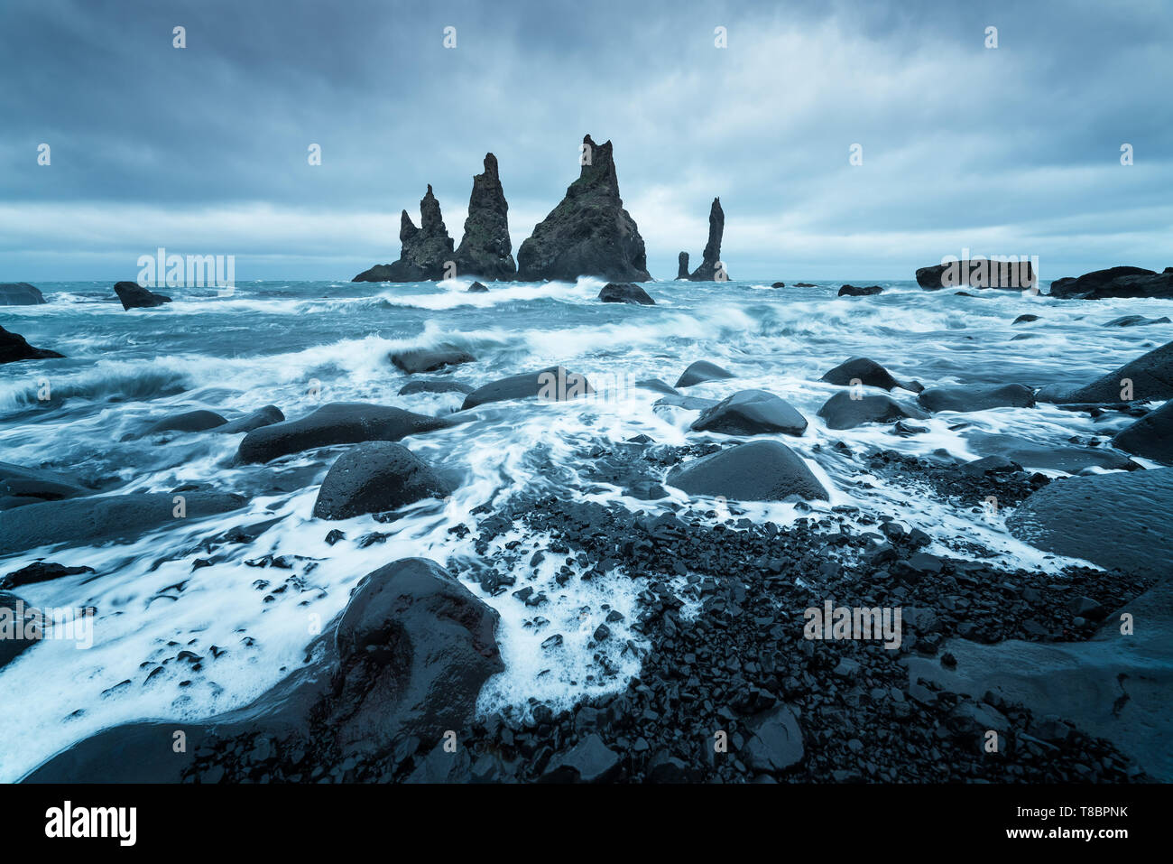 Trolls fingers. Reynisdrangar cliffs near the Vik town. Sullen landscape with the Atlantic Ocean. Tourist attraction of Iceland - Stock Image