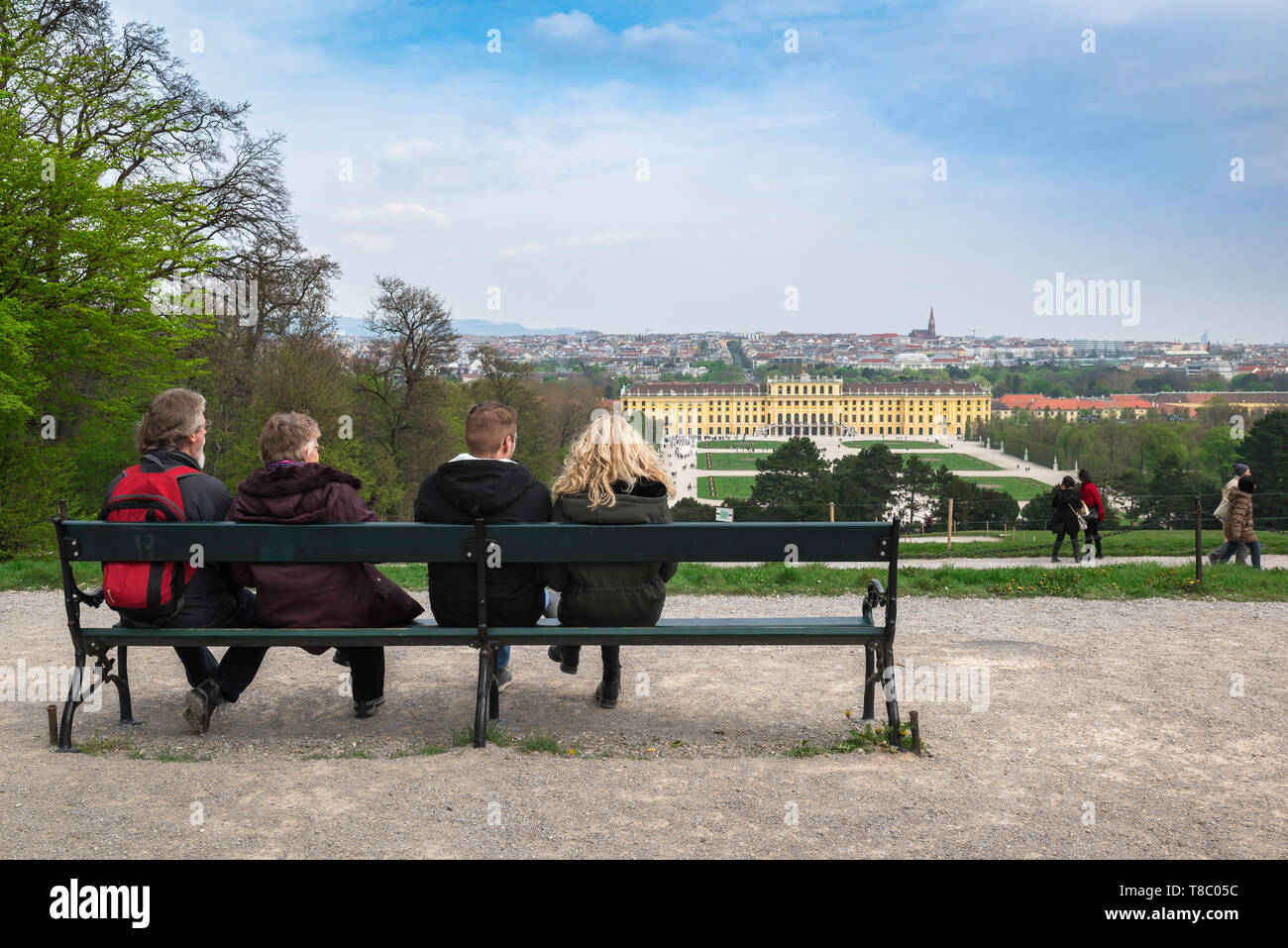 Vienna palace, rear view of tourists sitting on a bench looking towards the  palace and gardens of Schloss Schönbrunn in Vienna, Wien, Austria. - Stock Image