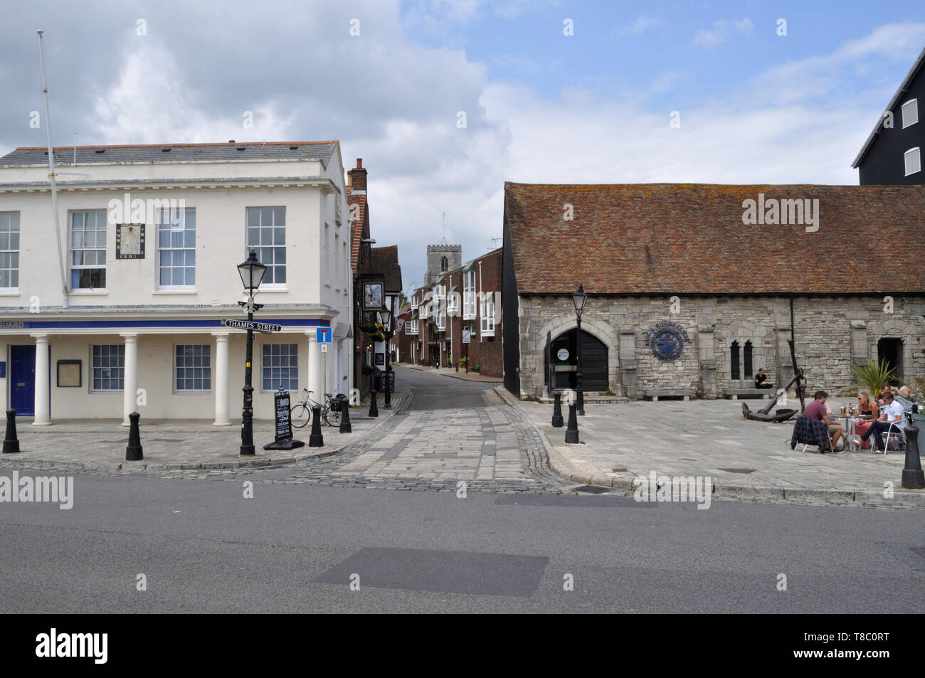 View along Thames Street, Poole, from the quay, with the tower of St James's church in the background. - Stock Image