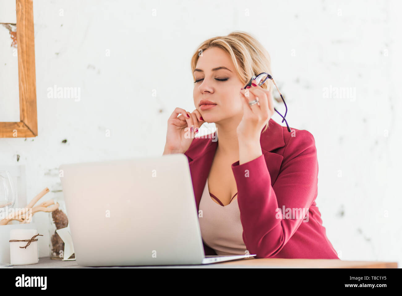Successful business woman enjoying her work in home office. Closeup photo of elegant charming lady smiling making up plan for weekend, dreaming after  Stock Photo