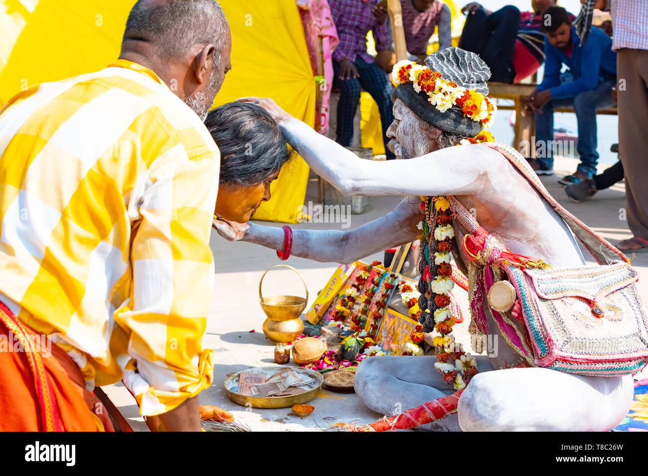 VARANASI, INDIA, MAR 10, 2019 - Unidentified Hindu Sadhu holy man, sits on the ghat near the Ganges river in Varanasi, India. - Stock Image