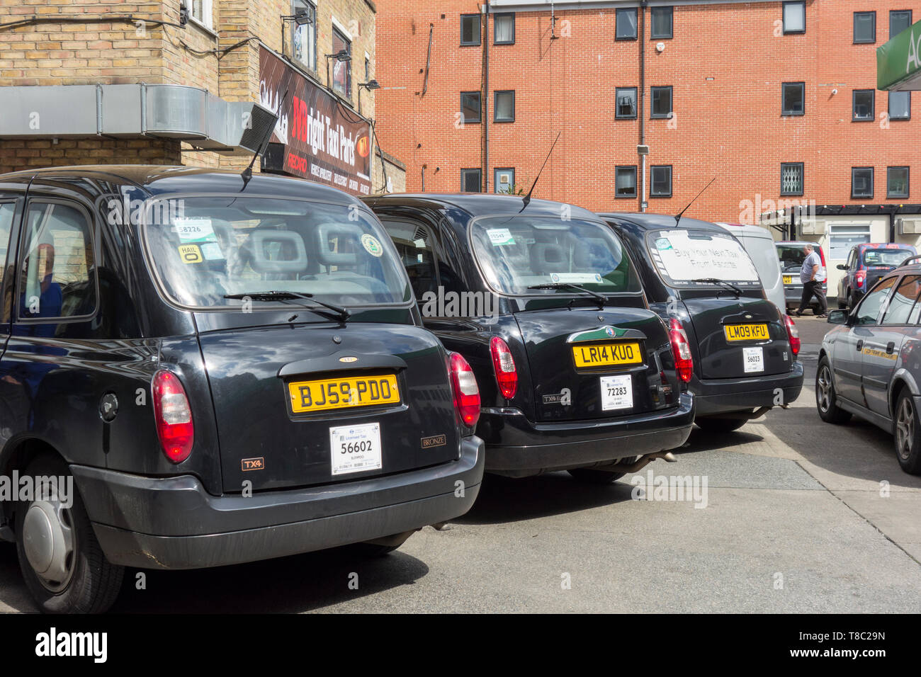 A row of London Black taxicabs in a garage in Southwark, London, UK - Stock Image