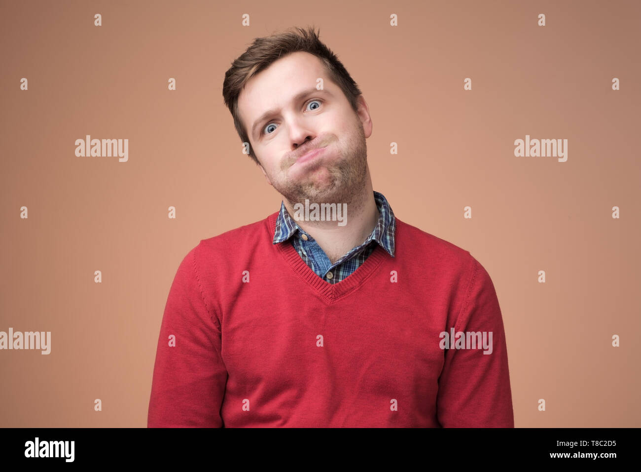 man in red sweater puffing his cheeks, feeling fed up as heis tired. - Stock Image