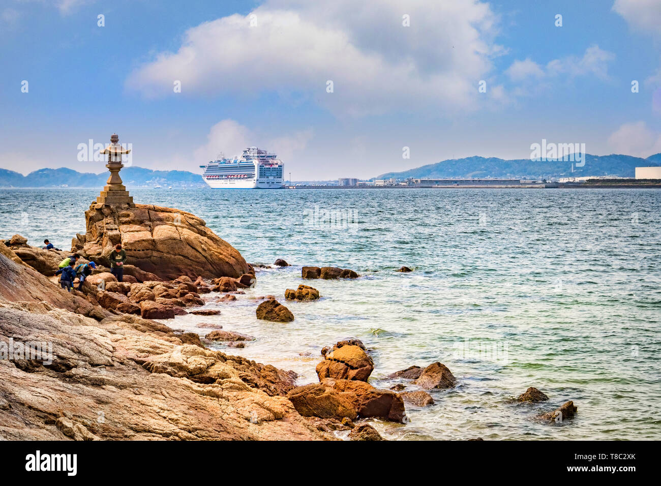 27 March 2019: Gamagori, Japan - The shore of the island of Takeshima, off Gamagori, with the cruise ship 'Diamond Princess' docked in the distance. Stock Photo
