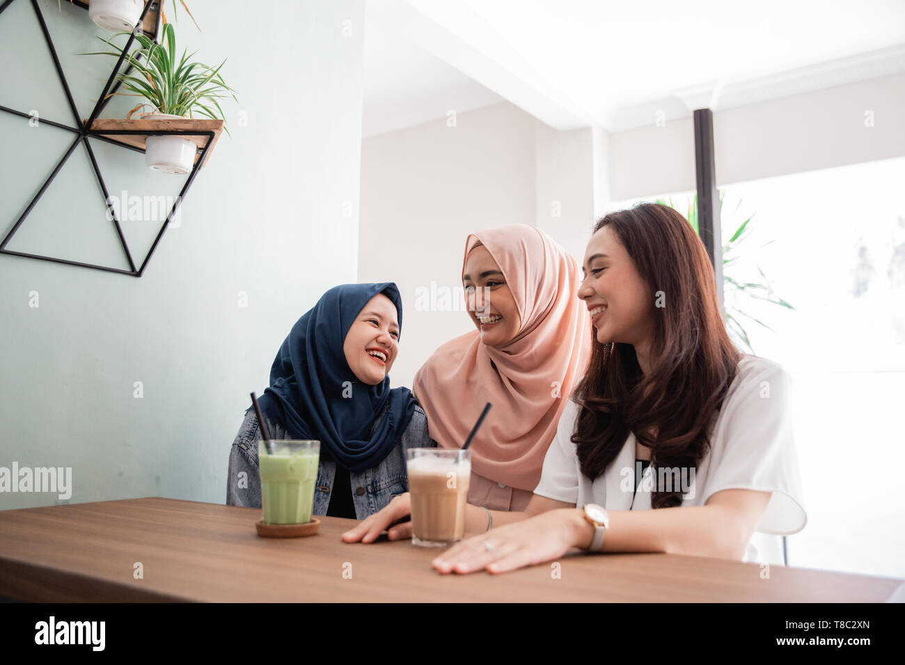 asian muslim woman bestfriend together in cafe  - Stock Image