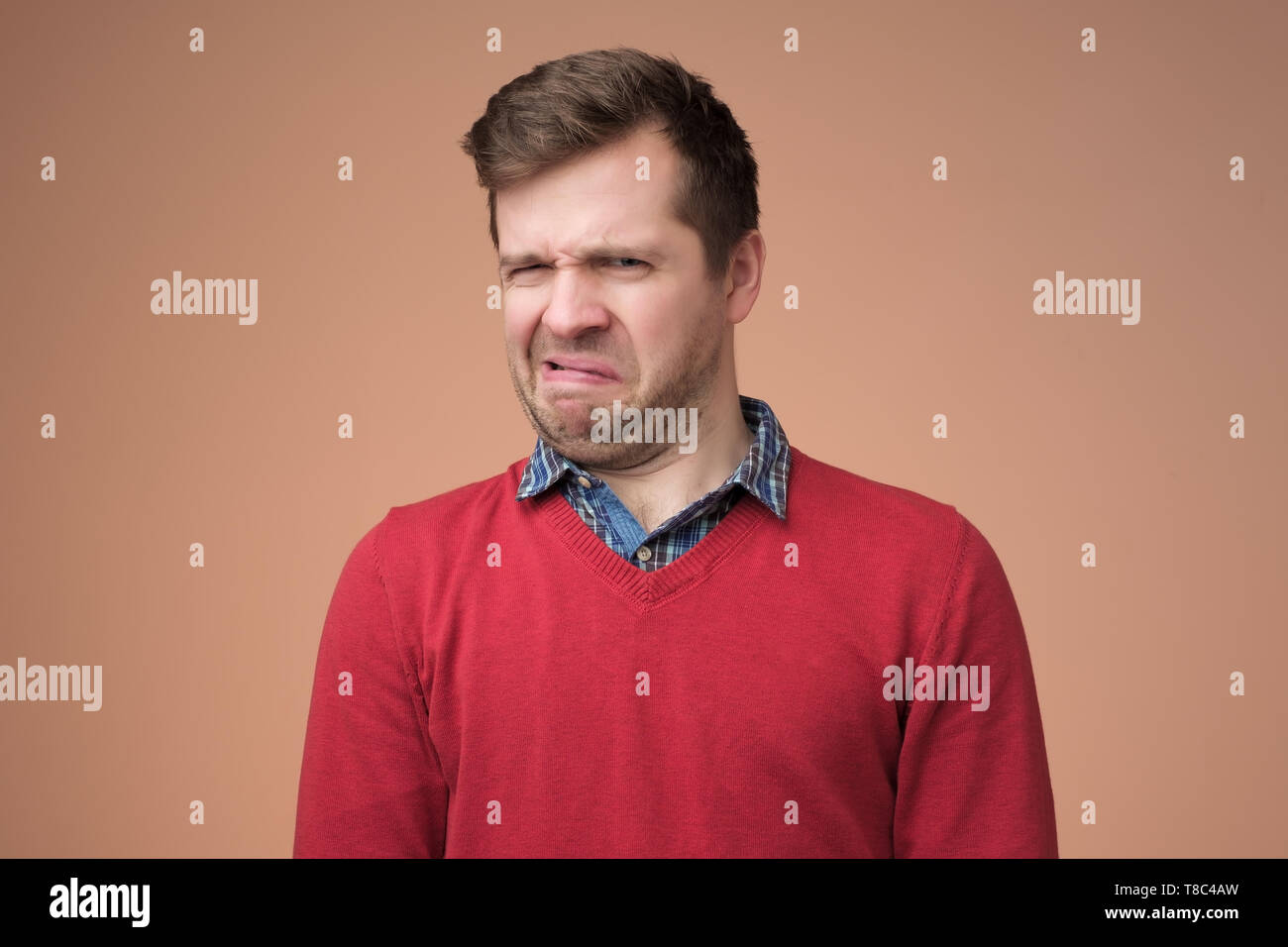 mature man in red sweater looking with disbelief expression - Stock Image