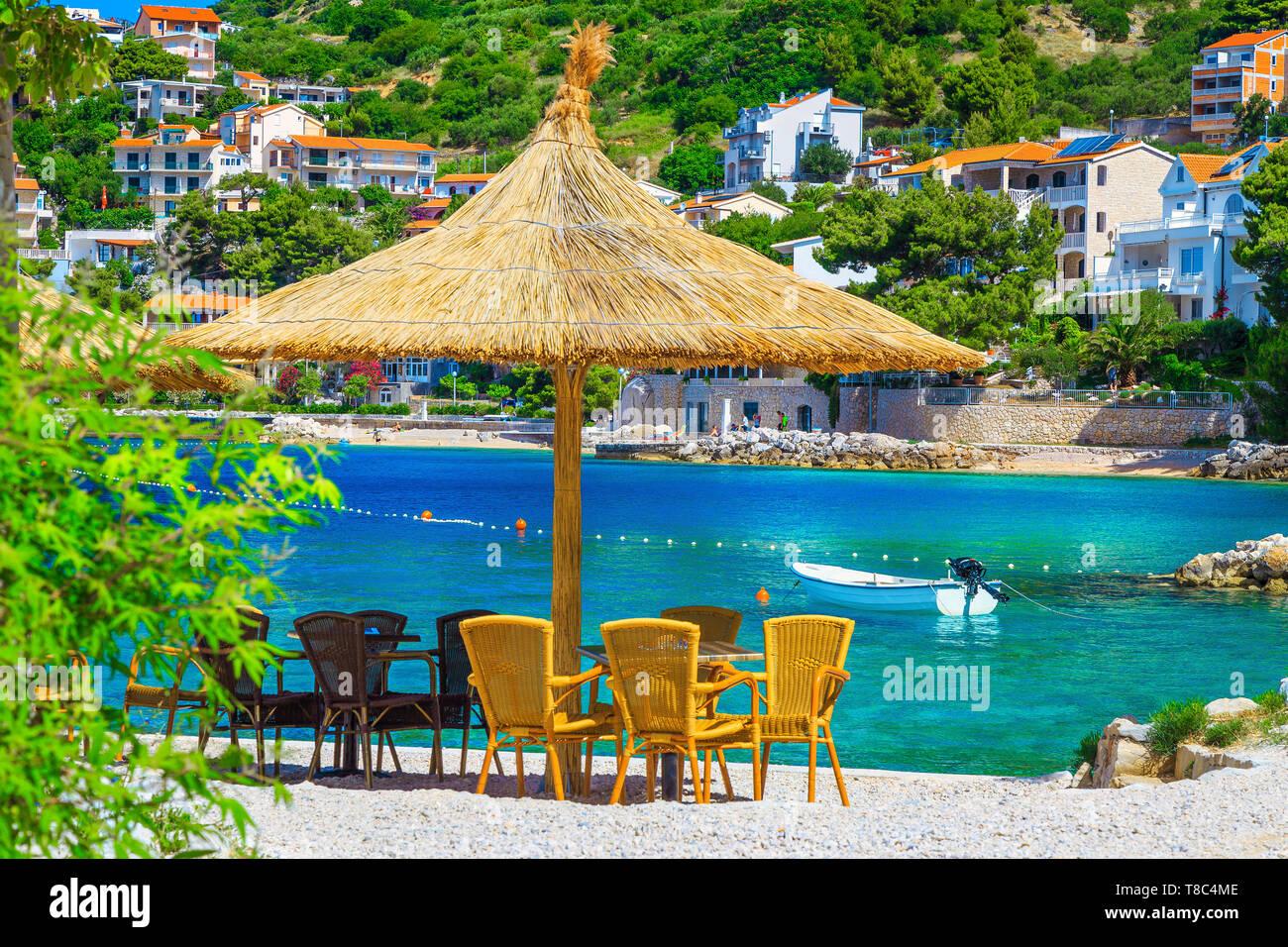 Fantastic summer holiday destination. Cozy outdoor tropical beach bar with straw parasols and beautiful view, Brela, Makarska riviera, Dalmatia, Croat - Stock Image