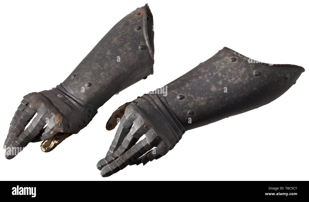 A pair of German gauntlets for cuirassiers, circa 1620 Fingered gauntlets with the original blackening. Metacarpus sliding on four lames and with ridged knuckle guard, attached to it complete finger scales with escutcheons on the sides. Long cuffs, reaching up to the elbows, with turned-down and simply roped edges. Length 45.5 cm each. Beautiful, untouched original condition with intact, original leather covering. historic, historical, defensive arms, weapons, arms, weapon, arm, fighting device, object, objects, stills, clipping, clippings, cut o, Additional-Rights-Clearance-Info-Not-Available Stock Photo