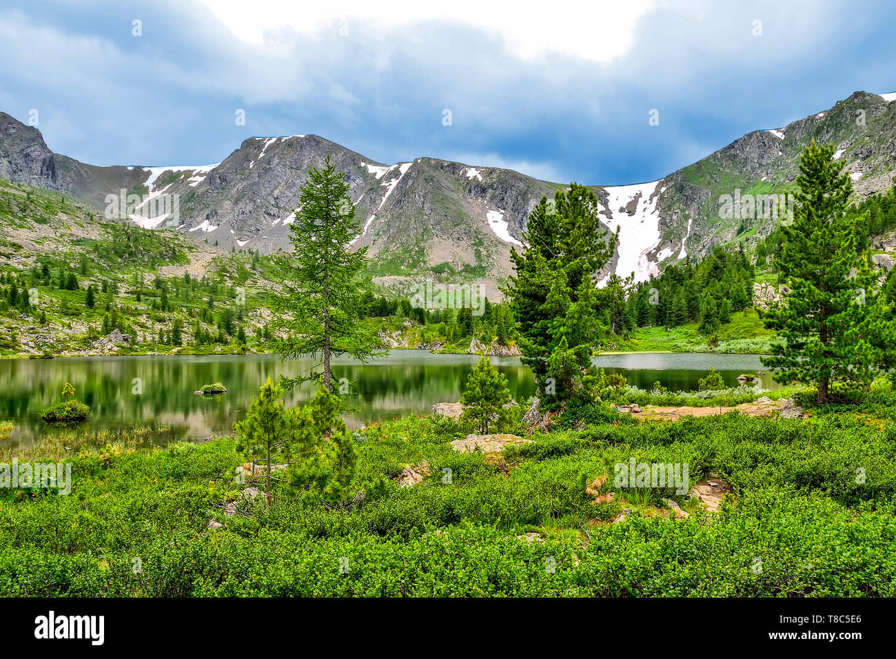 One from seven cleanest mountain Karakol lakes, located in the valley, at the foot of the Bagatash pass, Altai Mountains, Russia. Snow covered peaks a - Stock Image