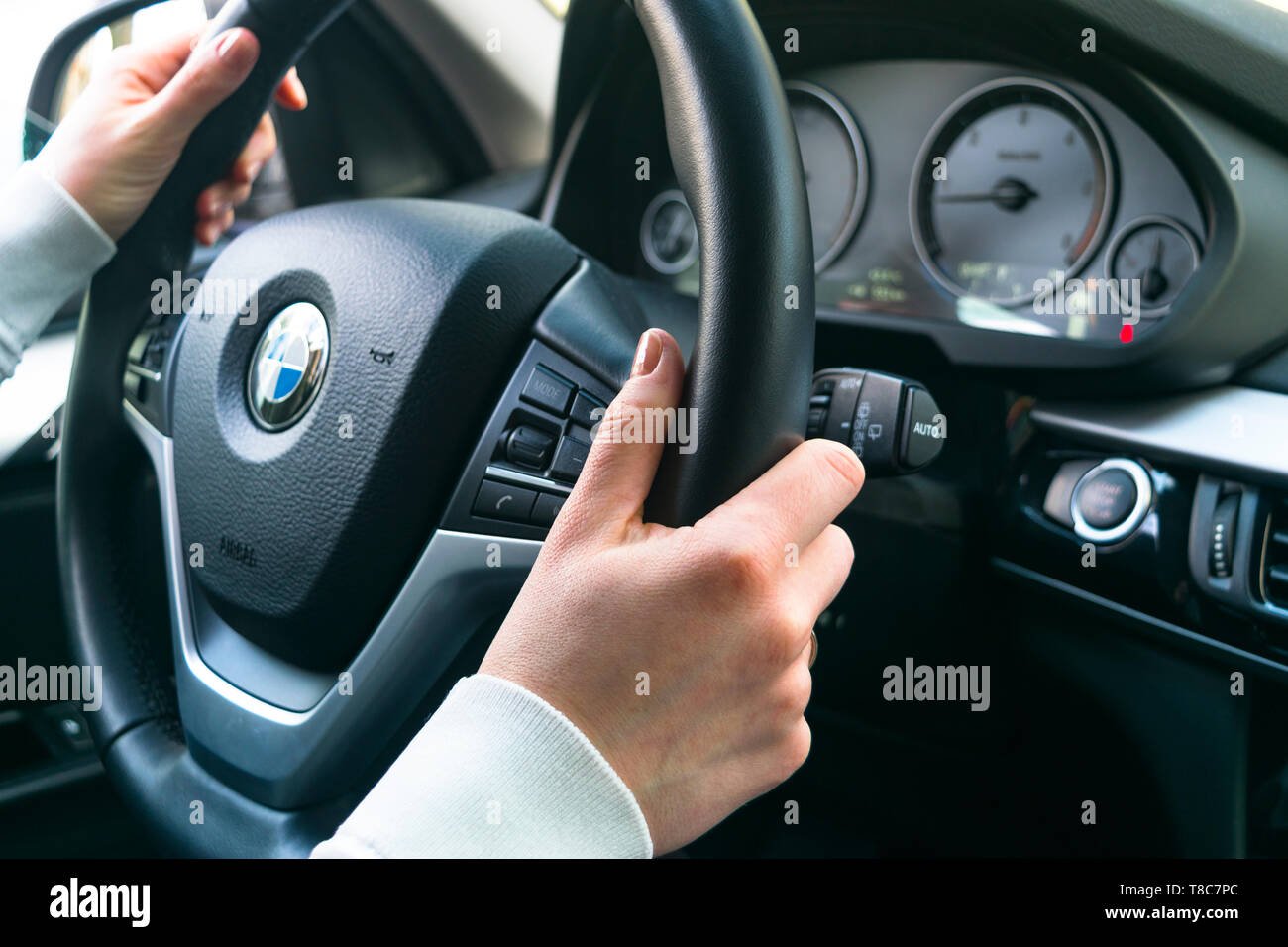 Sankt-Petersburg, Russia, November 16, 2017: Woman's hands on a steering wheel driving BMW X5 F15. Hands holding steering wheel. Modern Car interior d - Stock Image