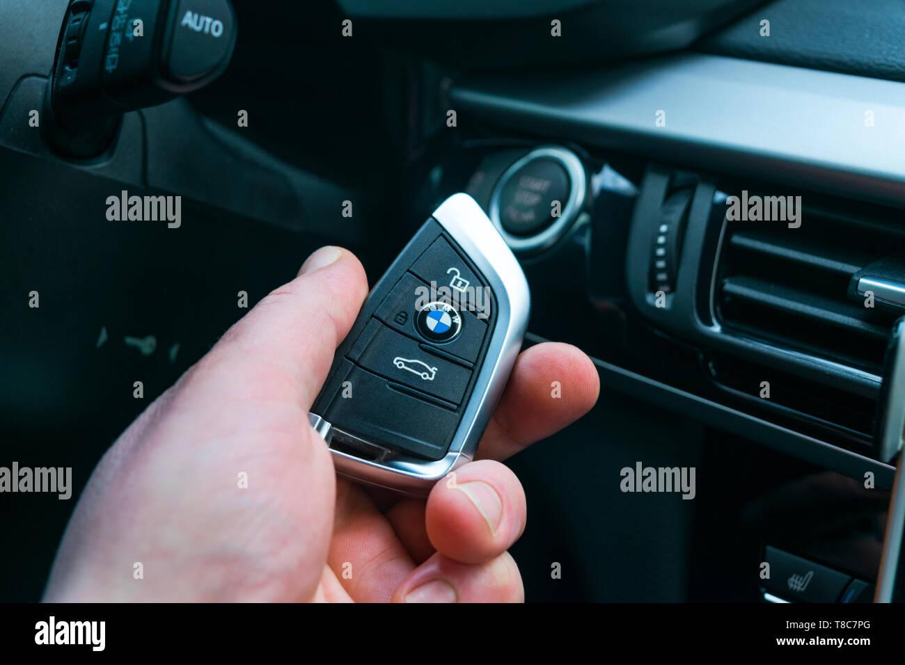 Sankt-Petersburg, Russia, November 16, 2017: BMW X5 F15 start car key in a male hand near start/stop push button. Modern car interior details. The key - Stock Image