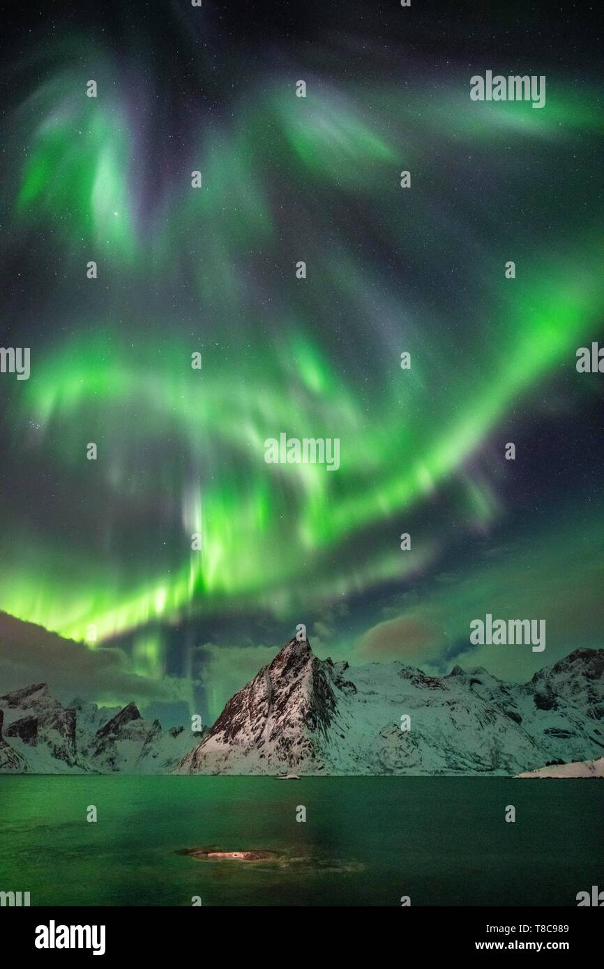 Northern Lights (Aurora Borealis) over mountains in winter, Olstinden, Hamnoy, Moskenesoy, Lofoten, Norway - Stock Image