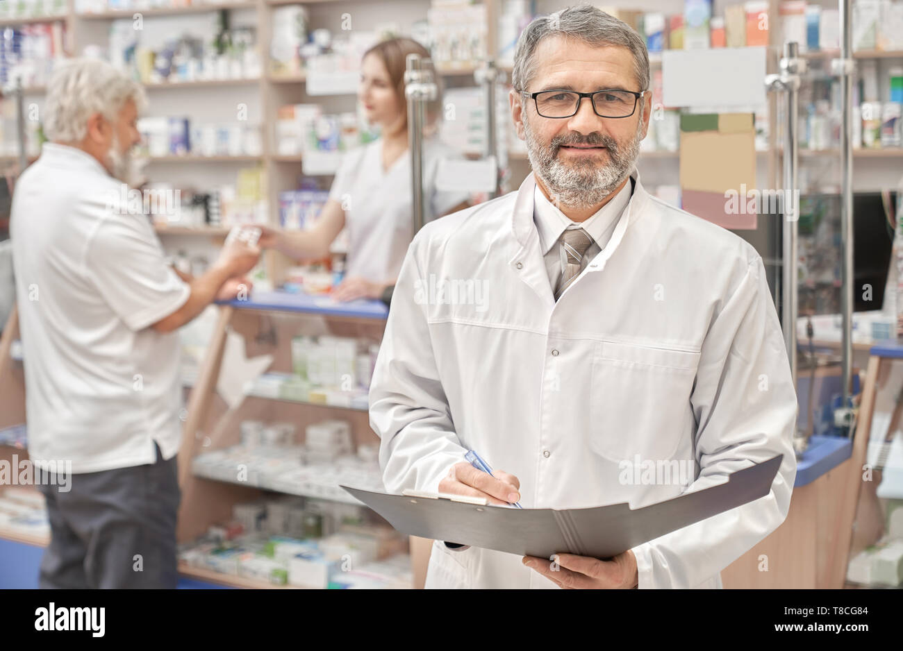 Handsome mature man working in drugstore as pharmacist. Professional specialist wearing in white lab coat and glasses. Bearded man holding folder and pen. Elderly man buiyng medicaments on background. - Stock Image
