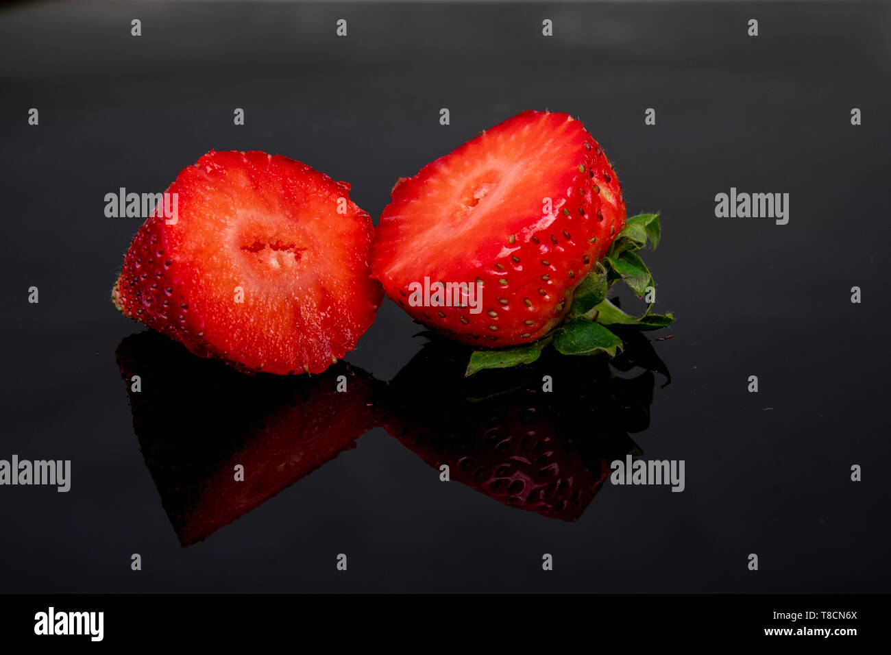 beautifully placed fresh delicious strawberries cut into two halves - Stock Image