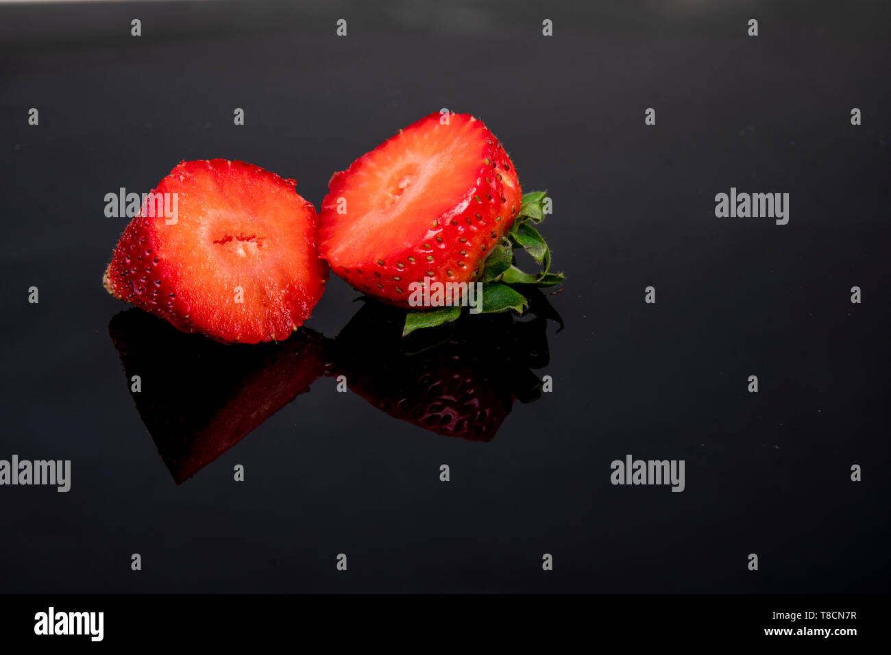 fresh strawberry rich in vitamins cut open on a dark background - Stock Image
