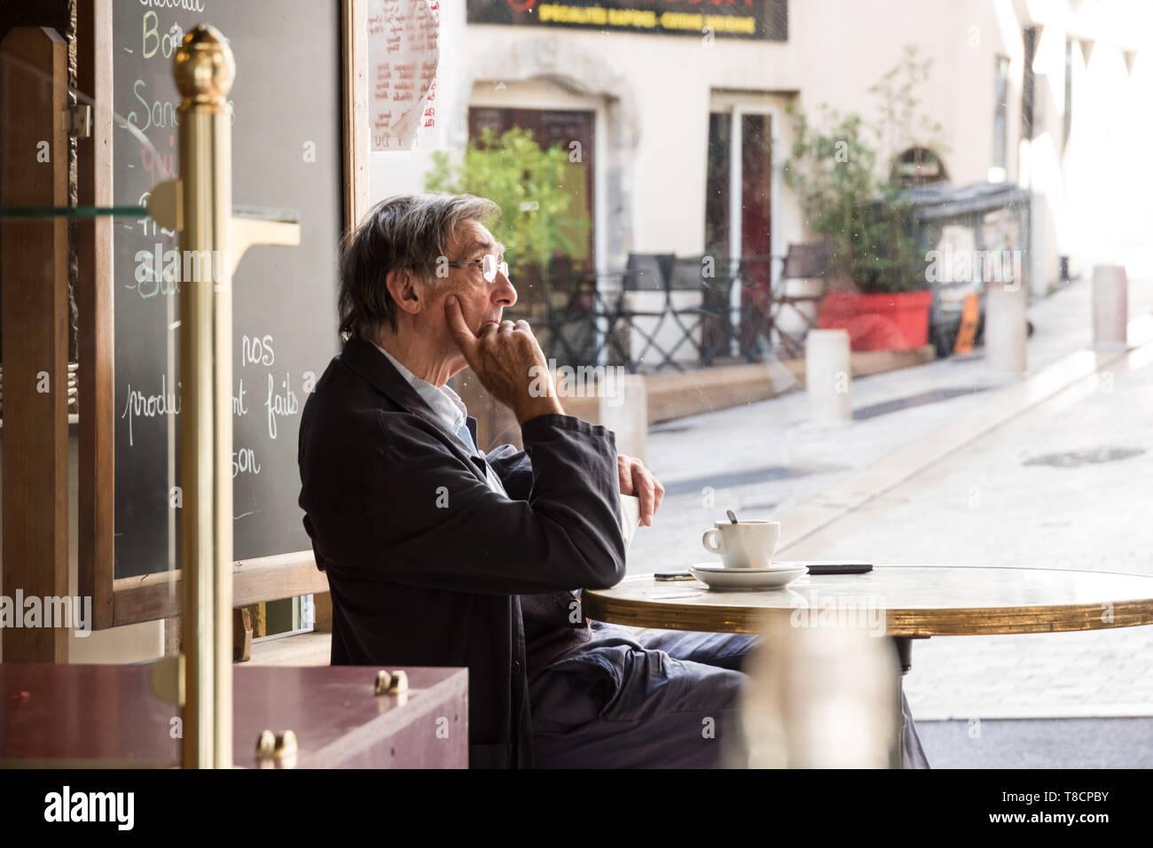 Lyon, 1. Arrondissement, Rue des Capucins, ein Mann sitzt in einem Cafe - Lyon, 1. Arrondissement, Rue des Capucins, a Man in a Cafe Stock Photo