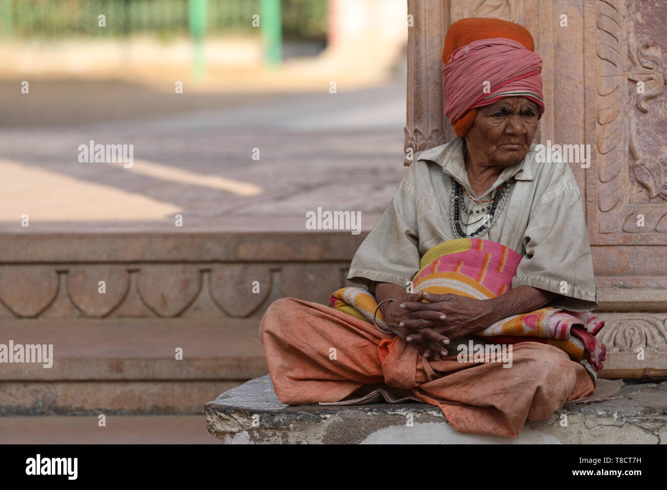 Old Woman sitting in front of Entrance to temple in Pushkar - Stock Image