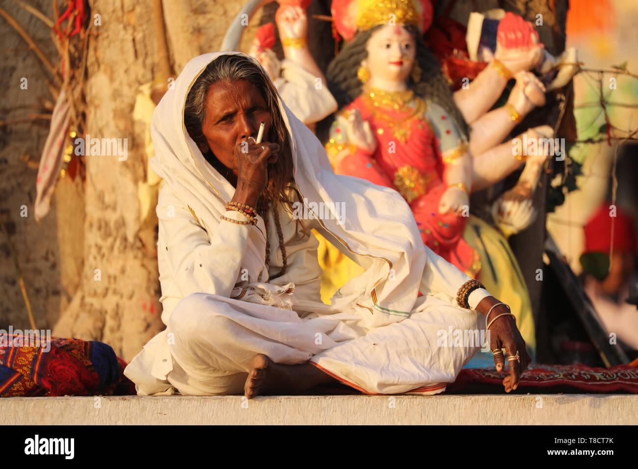 Old Woman sitting on holy tree and smoking - Stock Image