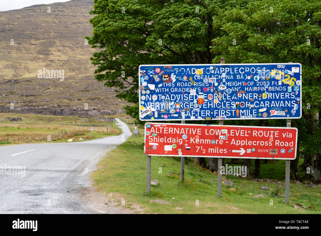 Warning signs covered in drivers' stickers at base of the Bealach na Ba pass on Applecross Peninsula on North Coast 500 scenic driving route in Scotla - Stock Image