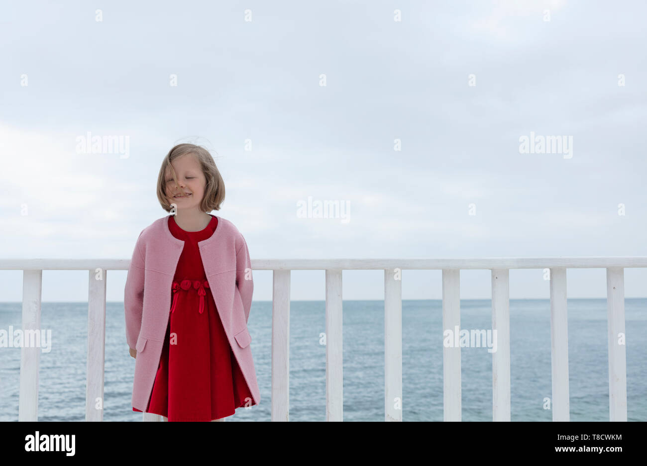Little funny girl (7 years old) in a pink coat and red dress, laughs, dances and sings on a white wooden pier on the sea. Selective focus. - Stock Image