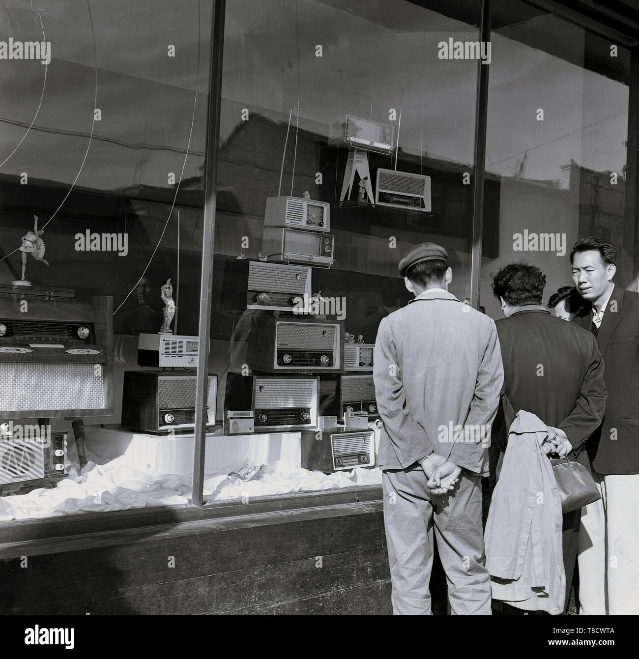 1950s, historical, Beijng, china, people looking through a store window at the range of radios on display in the shop. - Stock Image