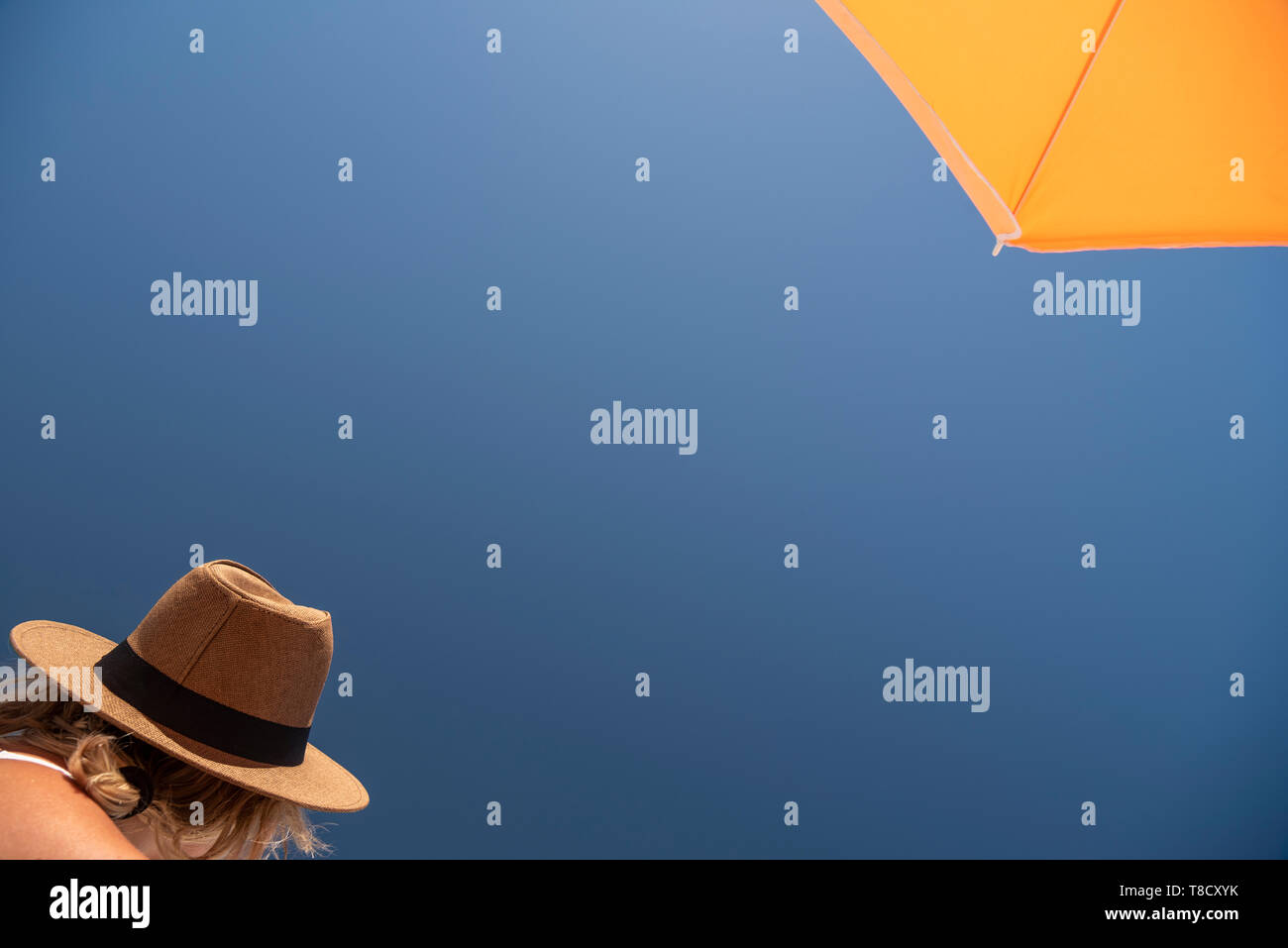 A holidaymaker wearing a hat and sitting under an ambrella Stock Photo