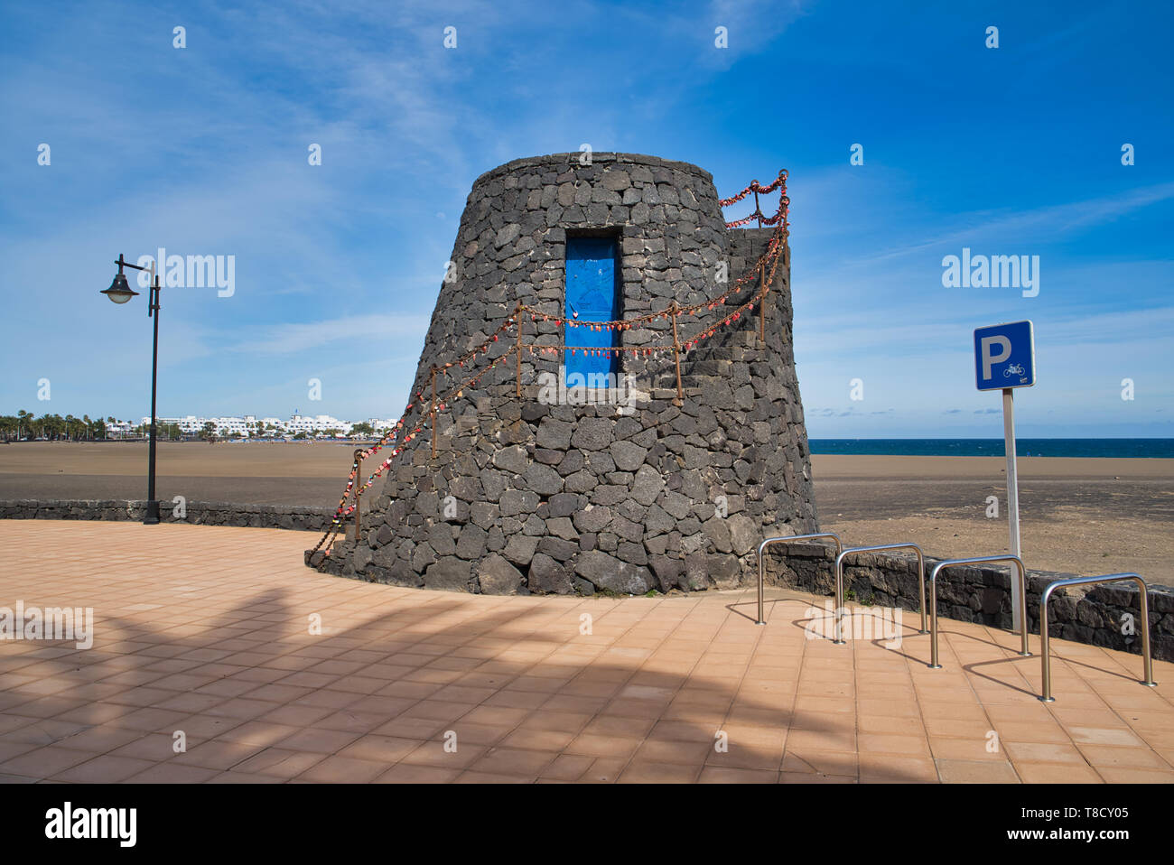 Tower of black lava stones, blue door and love locks on Promenade of