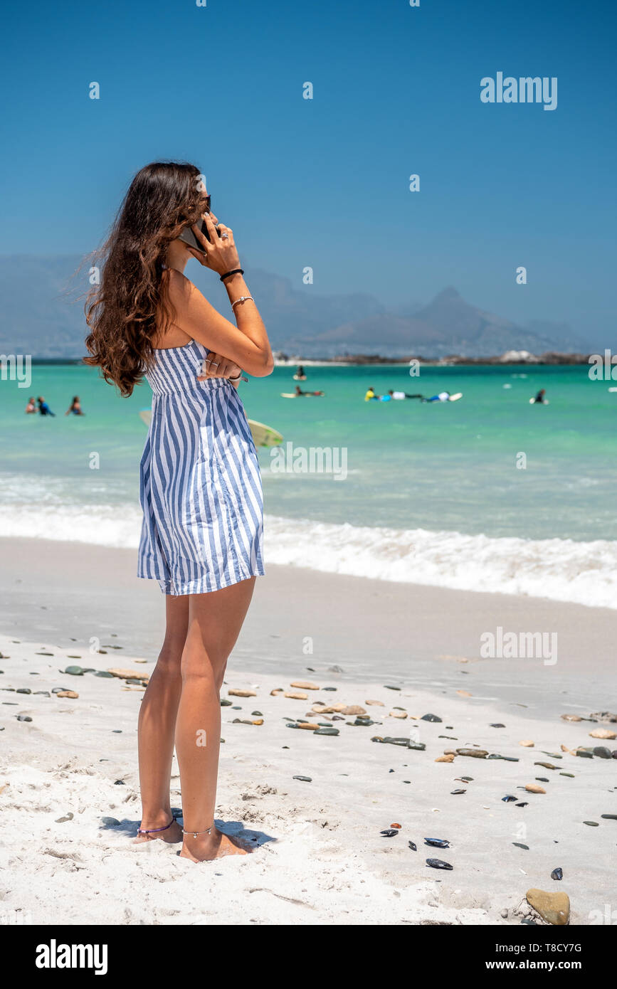 A young woman standing on the beach talking on her mobile phone - Stock Image