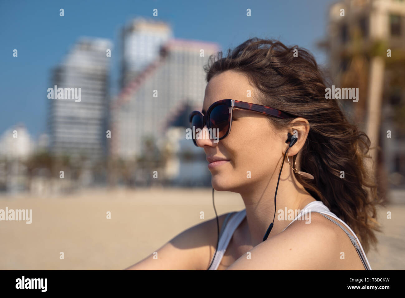 Woman seated on the beach contemplating the panorama while listening to music with earbuds - Stock Image