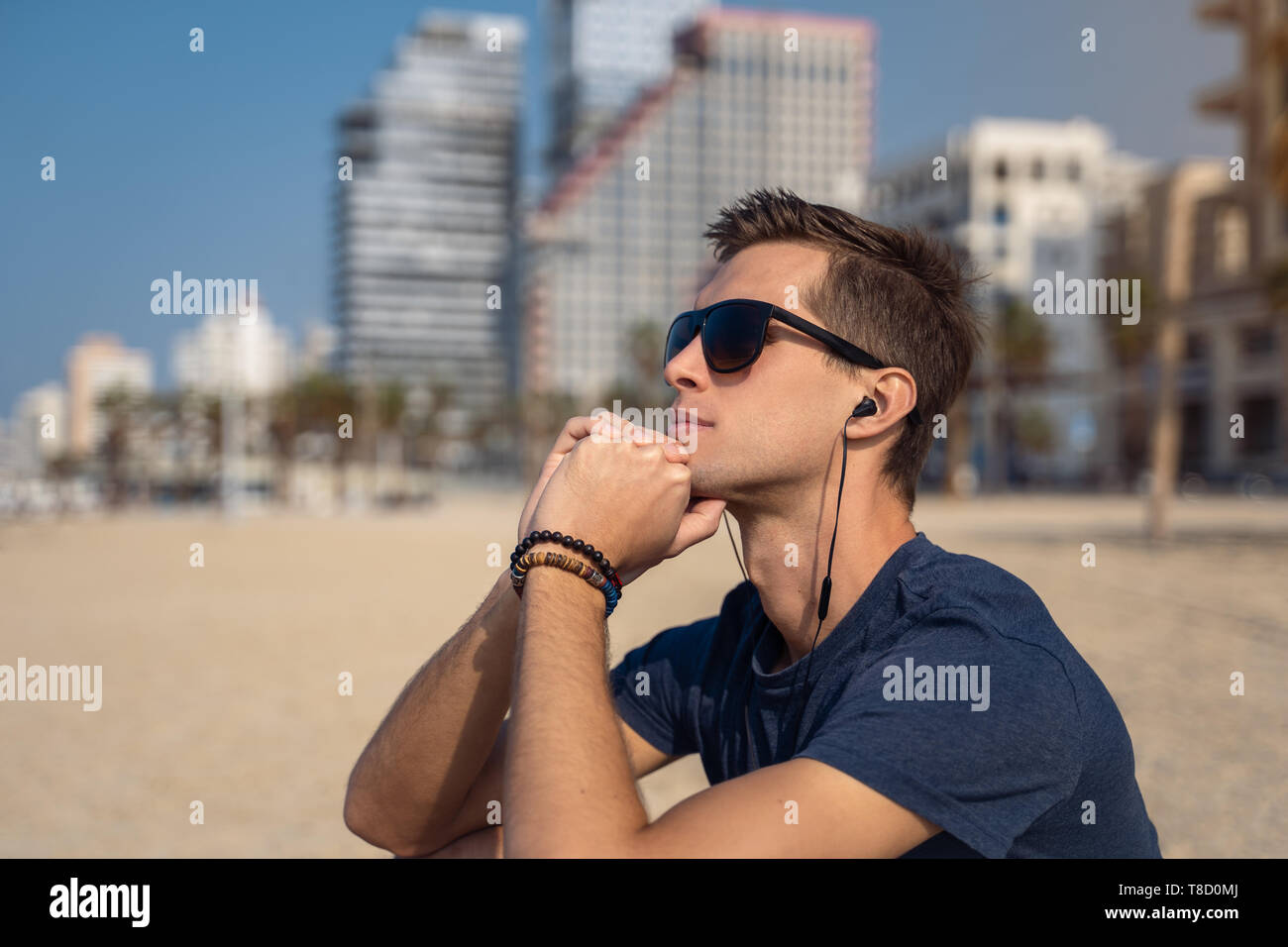 Man seated on the beach contemplating the panorama while listening to music with earbuds - Stock Image