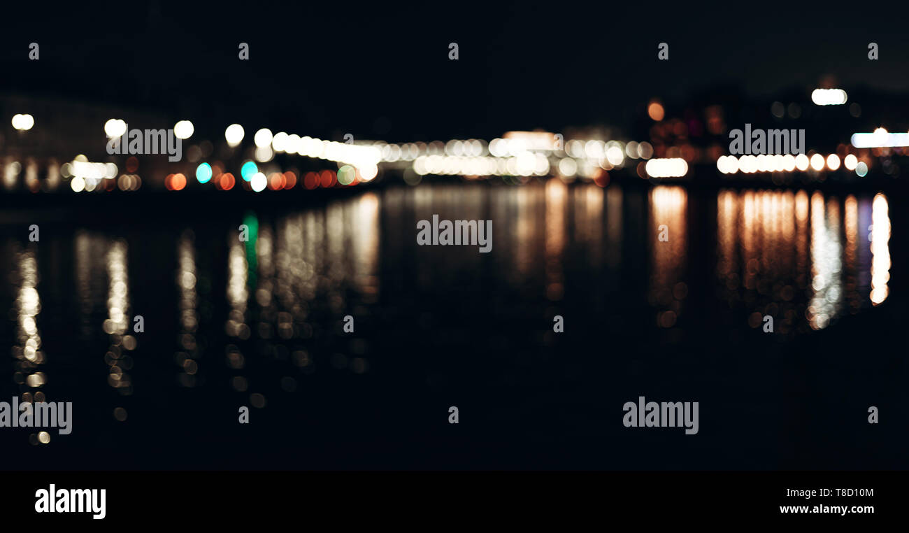Abstract background of colorful blurred city lights with bokeh effect reflected on water. - Stock Image