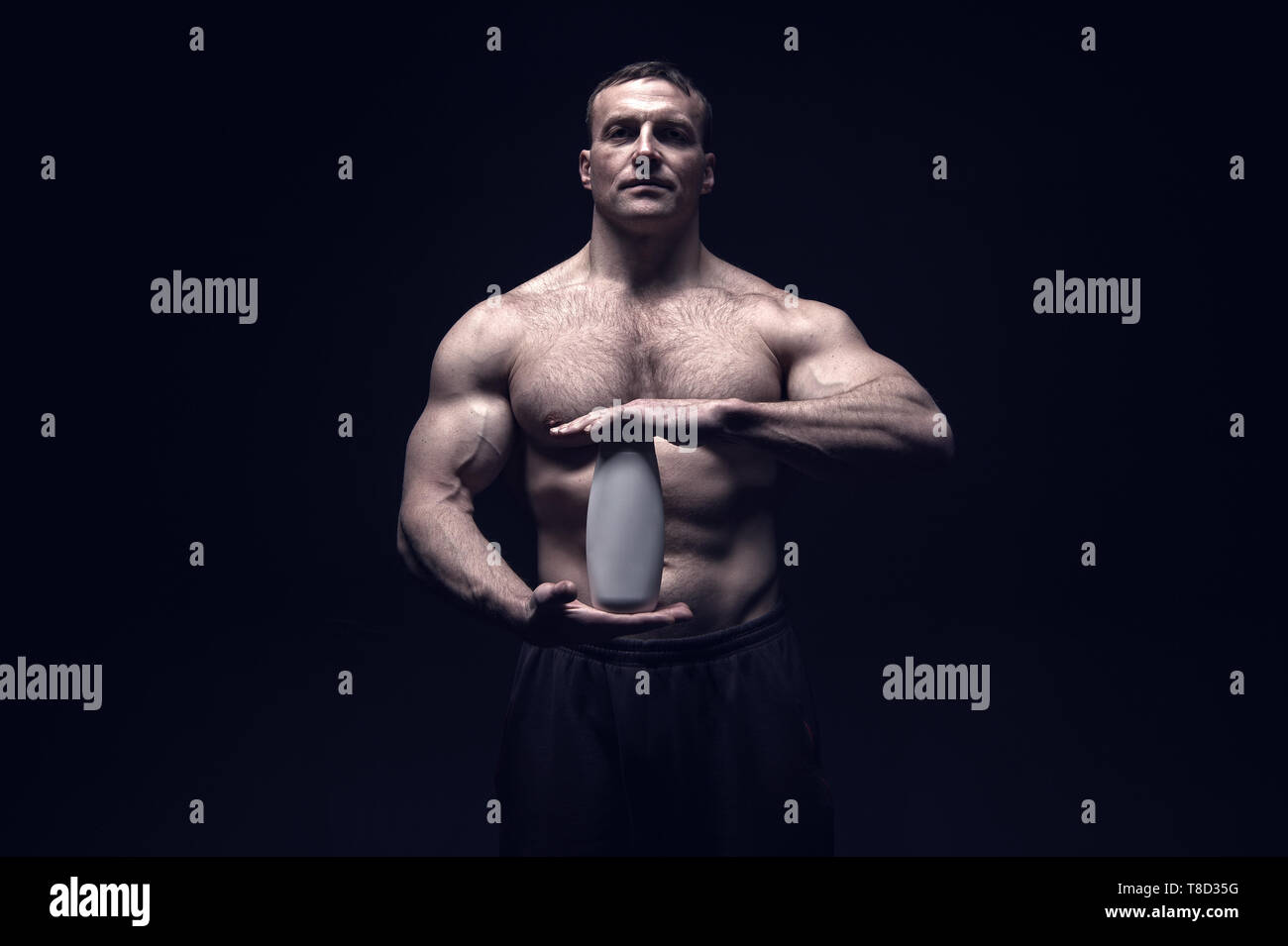 Bodybuilder hold shampoo or gel bottle. Man athlete with fit torso and ab. Bodycare and hygiene for sportsman. Spa bath or shower cosmetic after training in gym  - Stock Image