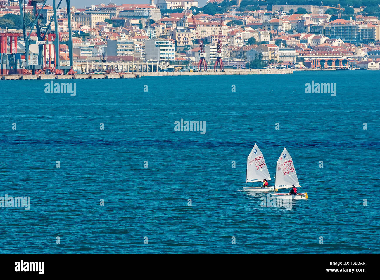 Lisbon, Portugal - April 03, 2010: sailboats in blue sea on cityscape. Yacht race on sunny day. Sea sailing championship. Regatta and yacht sailing sport. Travelling by water with adventure. - Stock Image