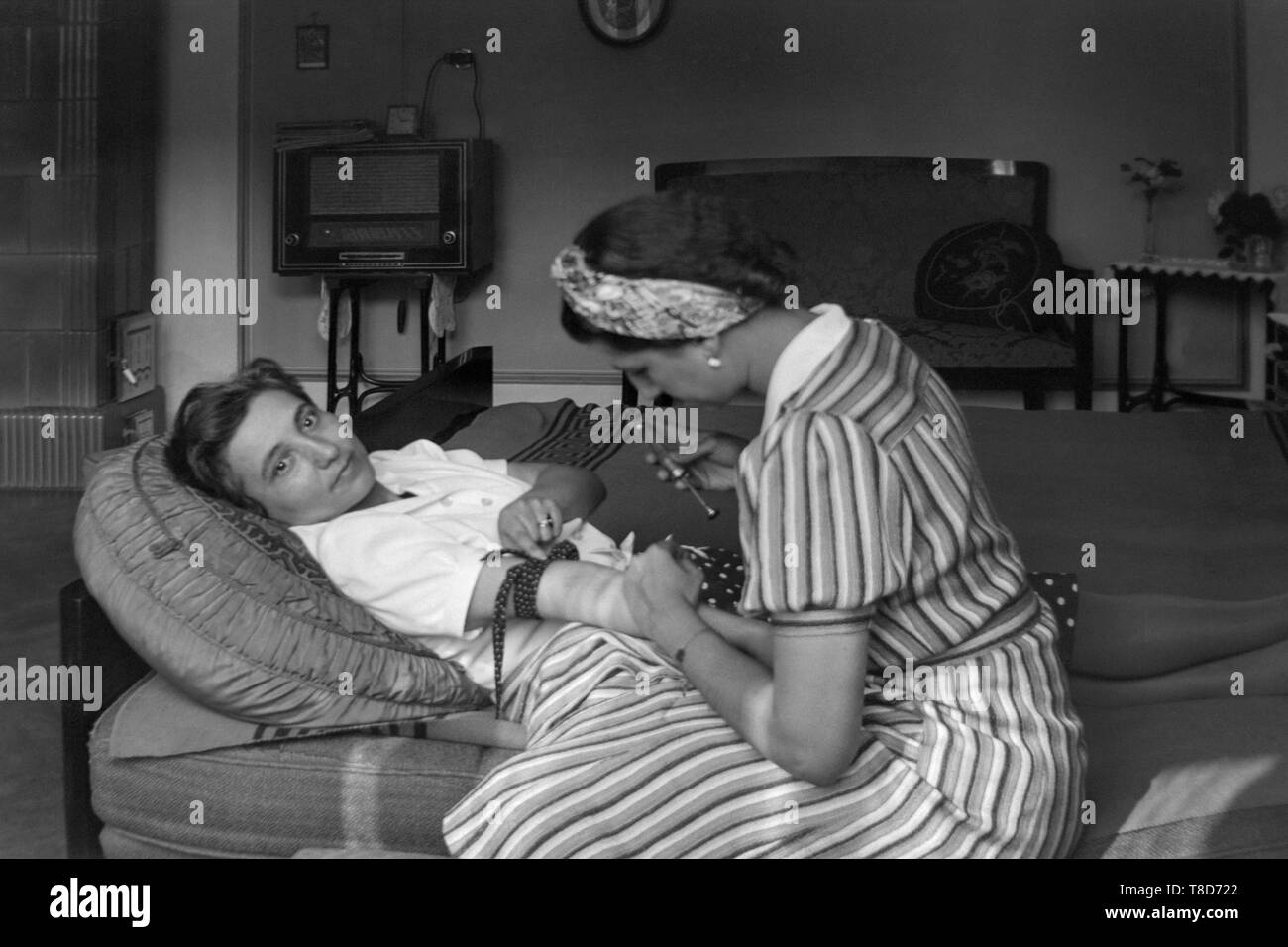 woman laying down on a couch preparing to have an injection in her arm by another lady 1930s hungary Stock Photo