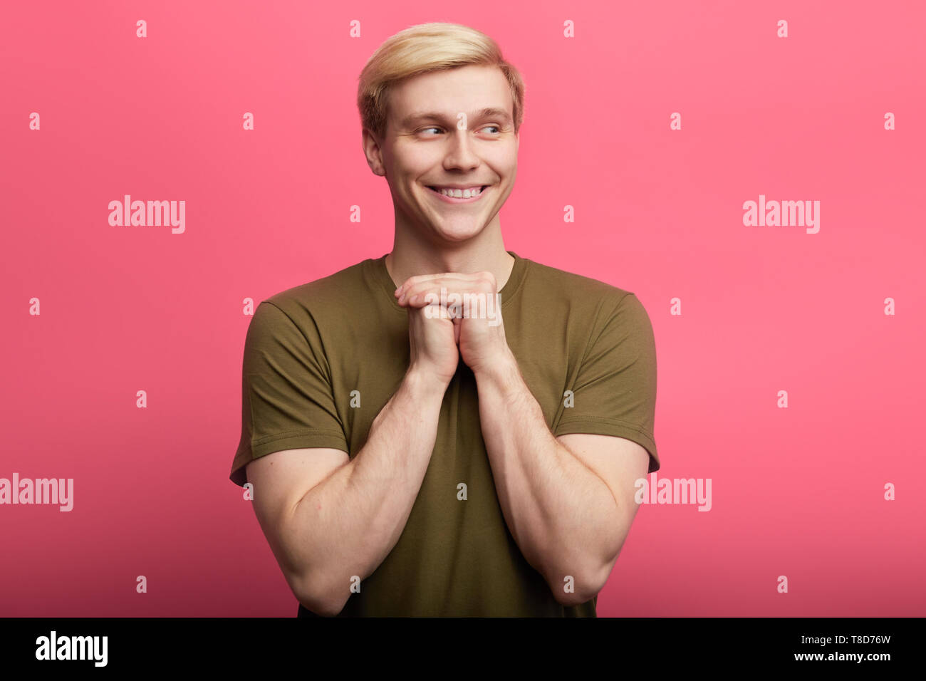 Cunning tricky smiling man standing with hand together , looking aside, over pink background. unfair game,interesting idea, plan for revenge - Stock Image