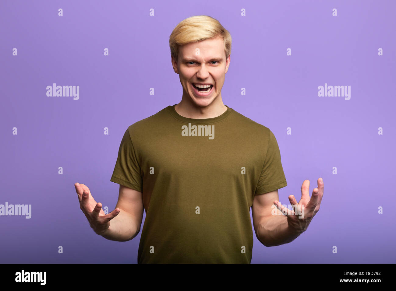 angry unhappy frustrated young man with arms out, shouting at somebody, negative emotion, feeling, frustration, anger. emotional man explaining something - Stock Image