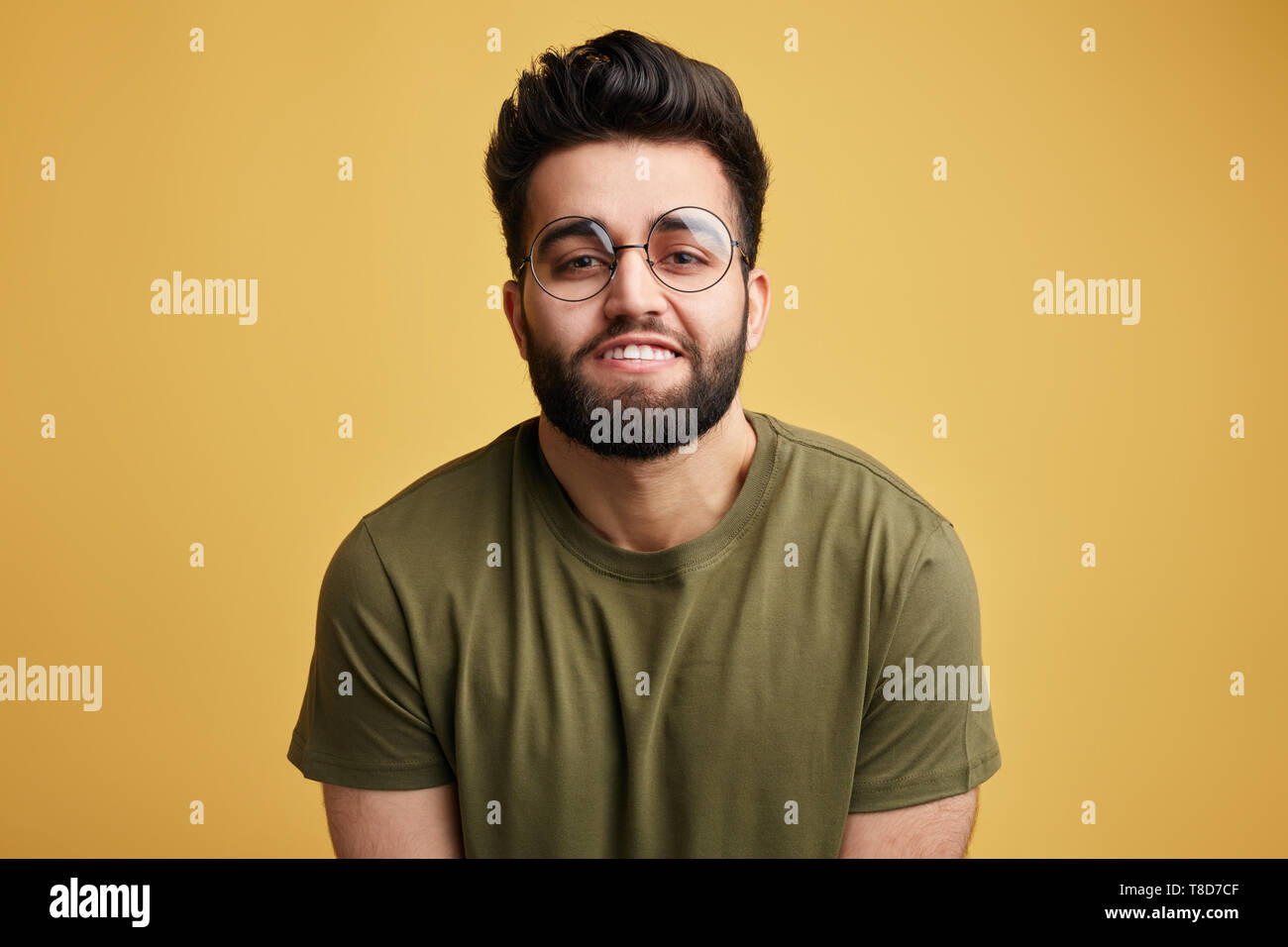 Attractive awesome positive harmless man in glasses showi ng his white teeth. close up photo. isolated yellow background. obedient guy.obedience concept - Stock Image